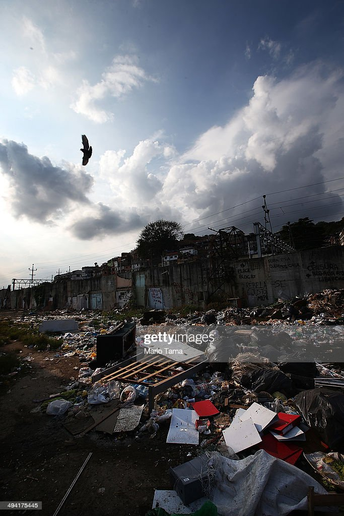 A bird flies over the remains of demolished homes and garbage in the Metro Mangueira favela, located near Maracana stadium, on May 17, 2014 in Rio de Janeiro, Brazil. The homes were thought to have been knocked down for a parking lot for the stadium, though that has yet to be built. The area has seen some people occupy certain dwellings. Evictions and demolitions have been occurring in Rio favelas ahead of the 2014 FIFA World Cup and Rio 2016 Olympic Games in spite of a housing shortage in the city. Rio's housing and urban planning goals include a planned five percent reduction of areas occupied by favelas by 2016. Alternative affordable housing, generally on the peripheries of the city, is unable to meet demand and some residents complain they have not received adequate compensation for demolished homes.