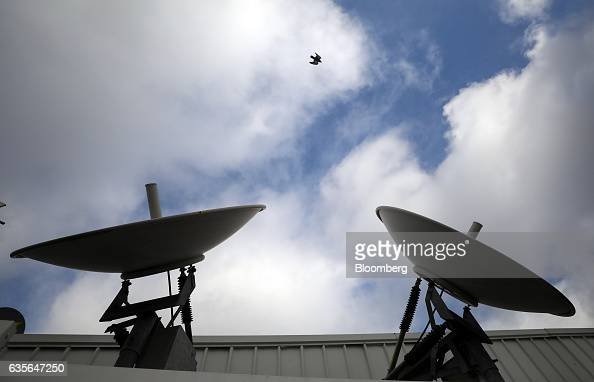 A bird flies past satellite dishes on the roof at Inmarsat Plc's headquarters in London UK on Thursday Feb 16 2017 Inmarsat Plc awarded Arianespace...