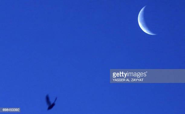 A bird flies past the waning crescent moon near the end of the Muslim holy month of Ramadan in Kuwait City on June 20 2017 / AFP PHOTO / Yasser...