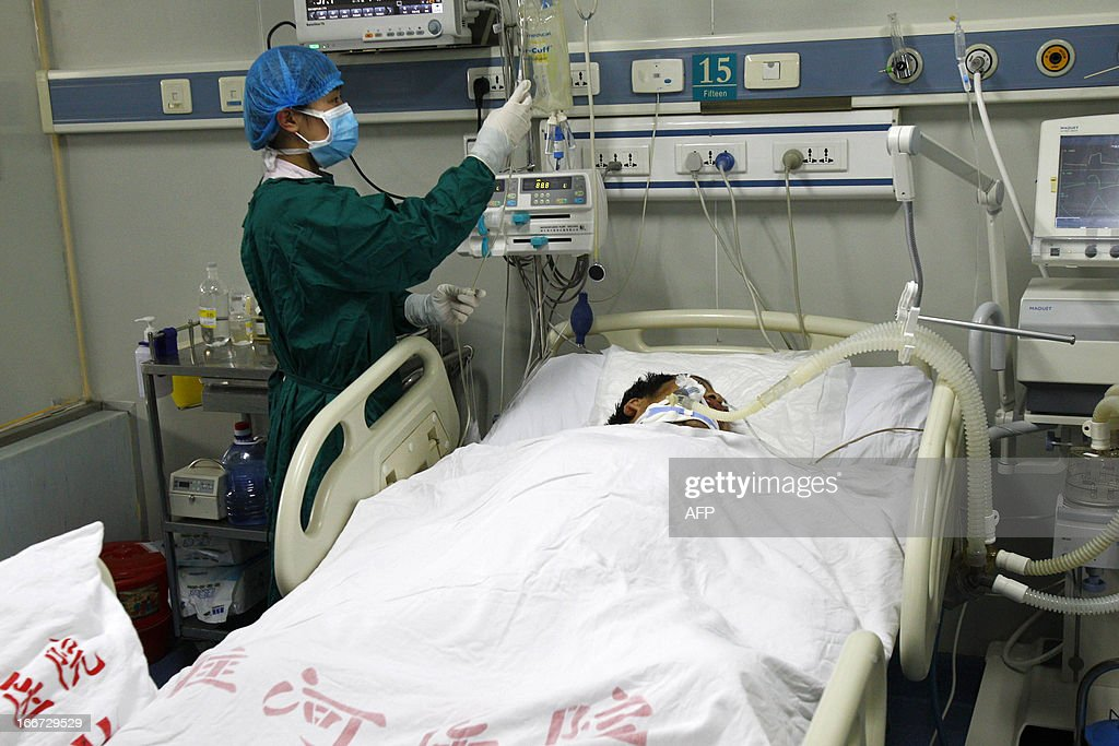 H7N9 bird flu patient Mr. Zhang, a 34-year-old cook, lies in his bed (C) after being treated in Luohe hospital in Kaifeng, central China's Henan province on April 16, 2013. China has won international praise for its transparency on the H7N9 strain, which has killed 14 people so far, in sharp contrast to criticism for trying to conceal the 2003 Severe Acute Respiratory Syndrome (SARS) epidemic. CHINA