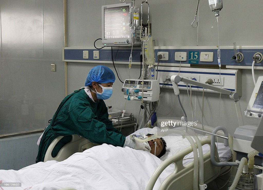 H7N9 bird flu patient Mr. Zhang, a 34-year-old cook, lies in his bed (C) after being treated in Luohe hospital in Kaifeng, central China's Henan province on April 16, 2013. China has won international praise for its transparency on the H7N9 strain, which has killed 14 people so far, in sharp contrast to criticism for trying to conceal the 2003 Severe Acute Respiratory Syndrome (SARS) epidemic. CHINA OUT AFP PHOTO