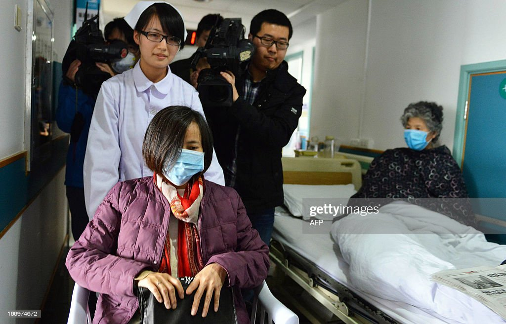 H7N9 bird flu patient, surnamed Jia (front L), is escorted from a hospital upon her recovery in Hangzhou, east China's Zhejiang Province on April 19, 2013. Experts from the UN's health agency are examining whether the H7N9 bird flu virus is spreading among humans, after a cluster of cases among relatives, but downplayed fears of a pandemic on April 19. CHINA OUT AFP PHOTO