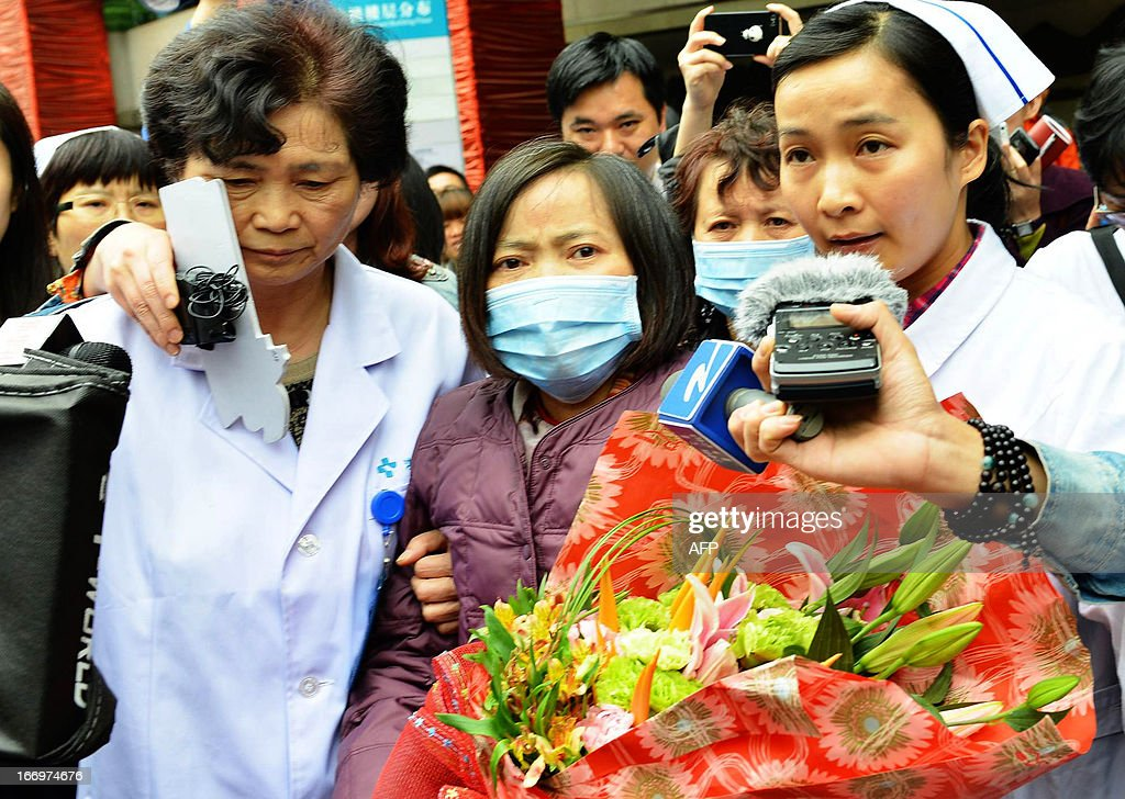H7N9 bird flu patient, surnamed Jia (C), is escorted from a hospital upon her recovery in Hangzhou, east China's Zhejiang Province on April 19, 2013. Experts from the UN's health agency are examining whether the H7N9 bird flu virus is spreading among humans, after a cluster of cases among relatives, but downplayed fears of a pandemic on April 19. CHINA