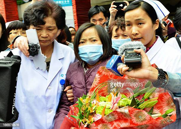 H7N9 bird flu patient surnamed Jia is escorted from a hospital upon her recovery in Hangzhou east China's Zhejiang Province on April 19 2013 Experts...