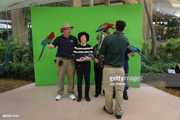 Bird handler Kenneth Gonzalez helps Ken Rubin Debra Rubin and Ruth Laitman as they interact with parrots at Jungle Island as Florida Governor Rick...