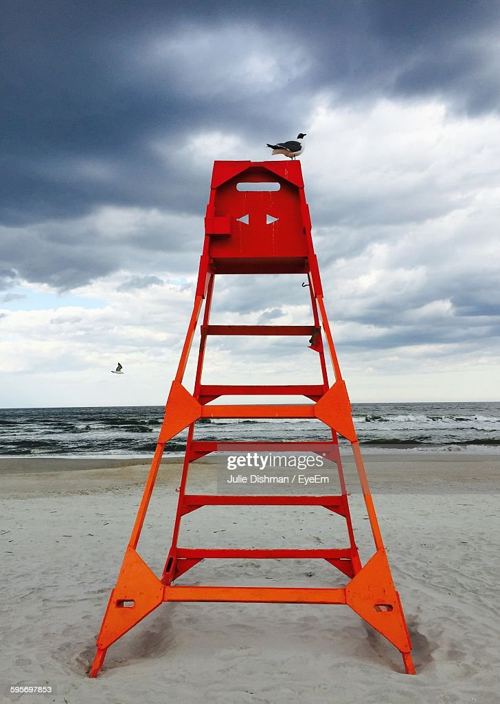bird perching on orange lifeguard chair at beach against cloudy sky