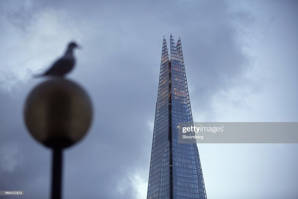 A bird sits on a street lamp near the Shard tower in London, U.K., on Thursday, Jan. 31, 2013. The Shard, which stands at 309.6 meters on London's South Bank, opens to the public on Feb. 1, and is owned by LBQ Ltd., which brings together the State of Qatar (the majority shareholder) and Sellar Property Group Ltd., with non-equity funding by Qatar National Bank. Photographer: Simon Dawson/Bloomberg via Getty Images