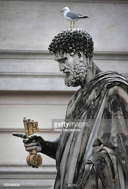 A bird sits on the head of a statue of St Peter in St Peter's Square on March 13 2013 in Vatican City Vatican Pope Benedict XVI's successor is being...