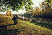 Man is watching birds with binoculars by the river in autumn.