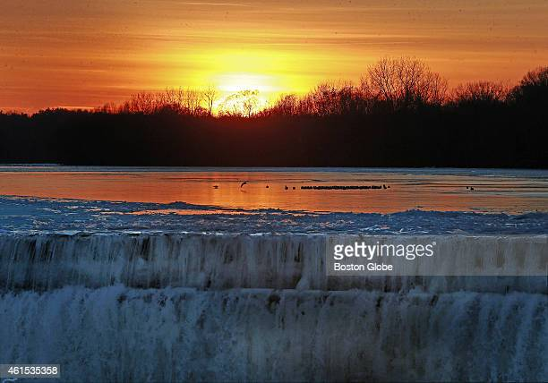 Birds are perched on patches of ice in the Merrimack River near the Great Stone Dam as the sun sets on a cold day