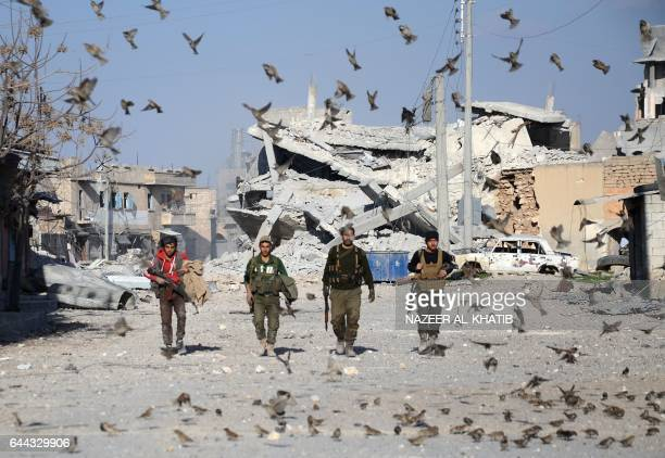 TOPSHOT Birds fly in front of Turkishbacked Syrian rebels walking in the northwestern border town of alBab on February 23 2017 after they fully...