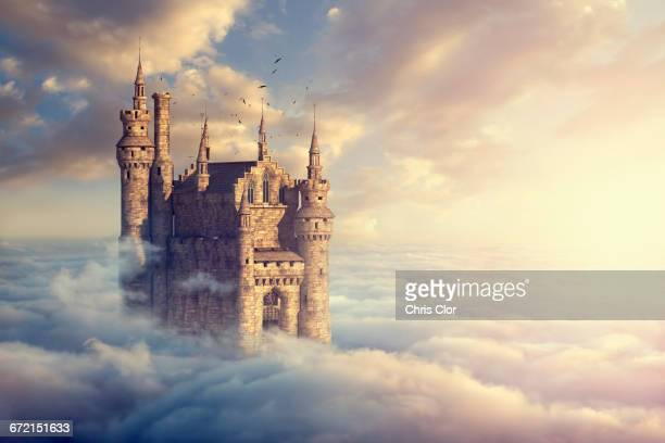 Birds flying around castle above clouds