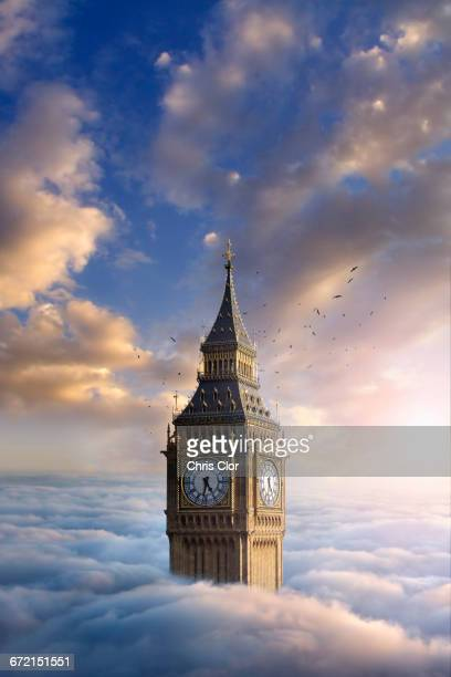 Birds flying around clock tower above clouds