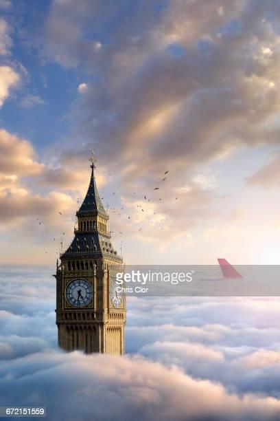 Birds flying around clock tower near airplane rudder above clouds