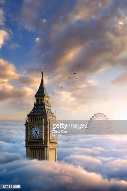 Birds flying around clock tower near ferris wheel above clouds