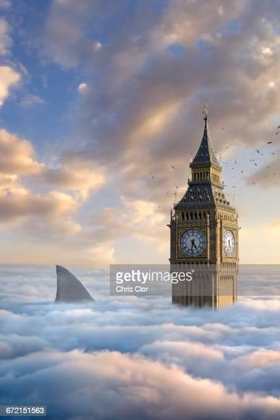 Birds flying around clock tower near shark fin above clouds