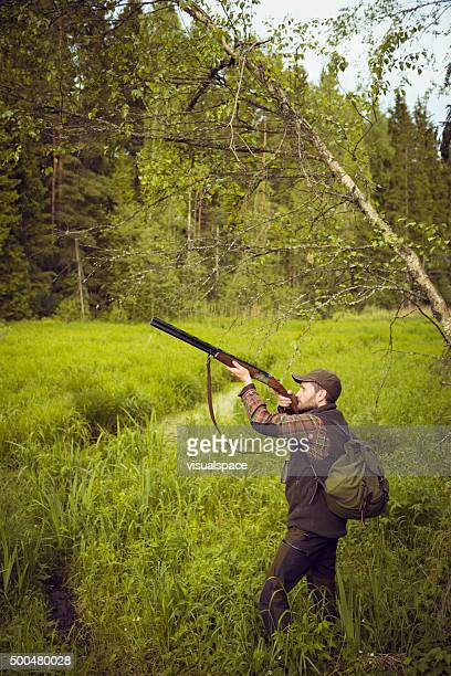 Birds Hunter Pointing Gun to the Sky in a Fen