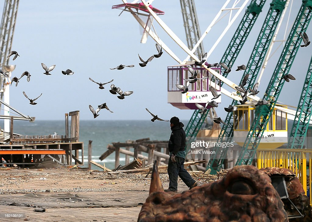 Birds take to flight as a worker cleans debris from the Fun Town Pier that was damaged by Superstorm Sandy, February 19, 2013 in Seaside Heights, New Jersey. Governor Chris Christie has estimated that damage in New Jersey caused by Superstorm Sandy could reach $37 billion. New Jersey.