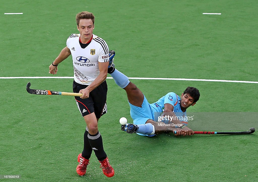 Birendra Lakra of India gets knocked down by Tom Meiling of Germany during the match between India and Germany during day three of the Champions Trophy at State Netball Hockey Centre on December 4, 2012 in Melbourne, Australia.