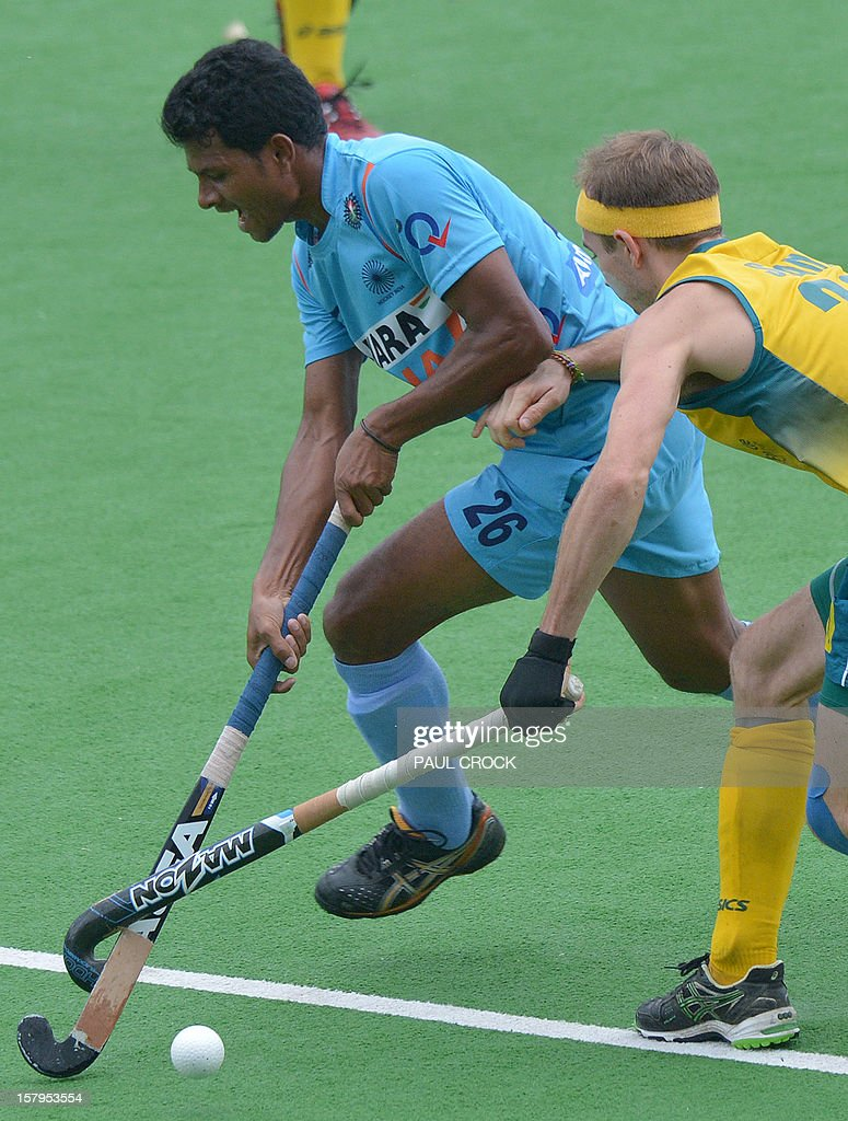 Birendra Lakra Singh of India (L) and Matthew Swann of Australia (R) tangle sticks during the second semi-final at the men's Hockey Champions Trophy tournament in Melbourne on December 8, 2012. IMAGE STRICTLY RESTRICTED TO EDITORIAL USE - STRICTLY NO COMMERCIAL USE AFP PHOTO / Paul CROCK