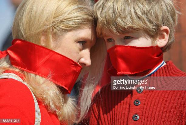 Birgit Cunningham and her son Jack CunninghamNuttall wear red gags over their mouths as they join in a protest at Piccadilly Circus London against...