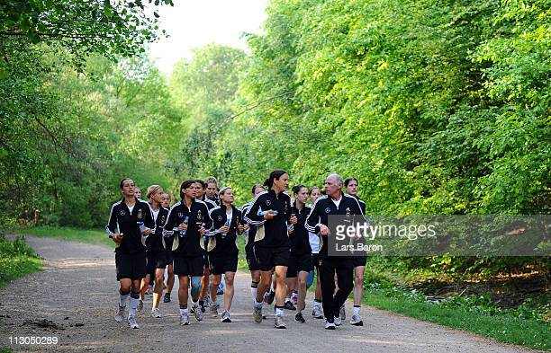 Birgit Prinz and her team mates warm up with fitness coach Norbert Stein during a German Women National Team training session at Villaforstpark on...