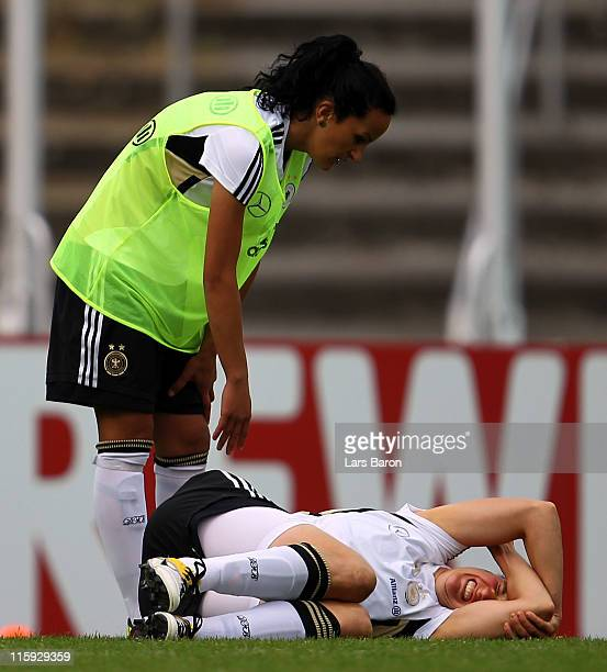 Birgit Prinz lies injured on the pitch next to Fatmire Bajramaj during a German Women National Team training session on June 12 2011 in Neu Isenburg...