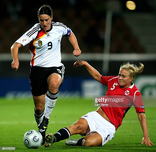Birgit Prinz of Germany is challenged by Anneli Giske of Norway during the UEFA Women's Euro 2009 SemiFinal match between Germany and Norway at the...
