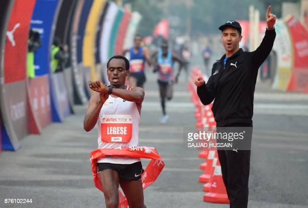 Birhanu Legese of Ethiopia checks the time after he crosses the finish line to win the Delhi Half Marathon in New Delhi on November 19 2017 In the...