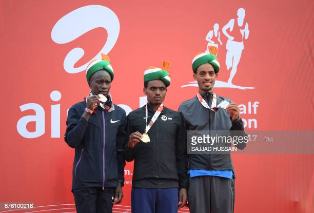 Birhanu Legese of Ethiopia poses with his gold medal with Andamlak Belihu of Ethiopia with his silver medal and Leonard Korir of US with his bronze...