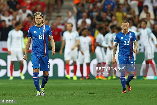 Birkir Bjarnason and Ari Skulason of Iceland react after England's first goal during the UEFA EURO 2016 round of 16 match between England and Iceland...