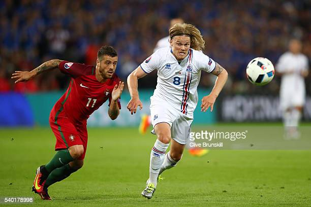 Birkir Bjarnason of Iceland and Vieirinha of Portugal compete for the ball during the UEFA EURO 2016 Group F match between Portugal and Iceland at...
