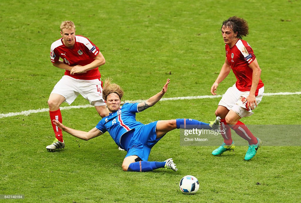 <a gi-track='captionPersonalityLinkClicked' href=/galleries/search?phrase=Birkir+Bjarnason&family=editorial&specificpeople=7137549 ng-click='$event.stopPropagation()'>Birkir Bjarnason</a> of Iceland goes down under the challenge of <a gi-track='captionPersonalityLinkClicked' href=/galleries/search?phrase=Julian+Baumgartlinger&family=editorial&specificpeople=4228877 ng-click='$event.stopPropagation()'>Julian Baumgartlinger</a> of Austria and <a gi-track='captionPersonalityLinkClicked' href=/galleries/search?phrase=Marc+Janko&family=editorial&specificpeople=2157344 ng-click='$event.stopPropagation()'>Marc Janko</a> of Austria during the UEFA EURO 2016 Group F match between Iceland and Austria at Stade de France on June 22, 2016 in Paris, France.