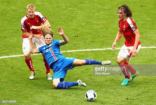 Birkir Bjarnason of Iceland goes down under the challenge of Marc Janko of Austria and Julian Baumgartlinger of Austria during the UEFA EURO 2016...