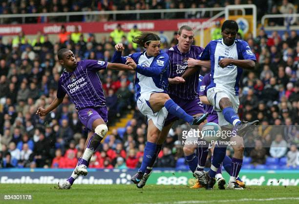 Birmingham City's Mauro Zarate battles for the ball with Manchester City's Fernandes Gelson and Richard Dunne