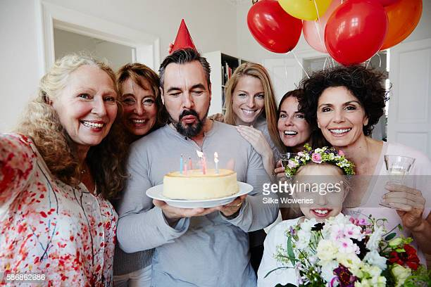 birthday boy blow out candles while good friends taking a self-portrait