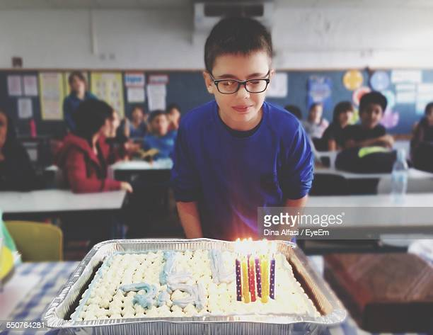 Birthday Boy Standing In Front Of Lit Cake In Classroom