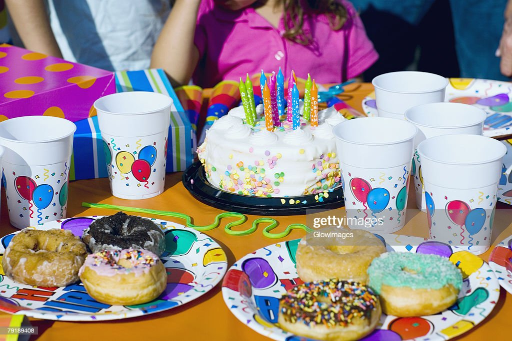 Birthday cake and donuts with presents on a table : Foto de stock