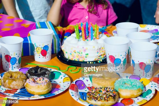 Birthday cake and donuts with presents on a table : Stock Photo