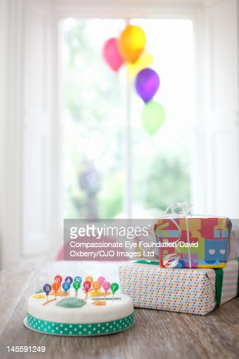 Birthday cake and presents on table : Stock Photo