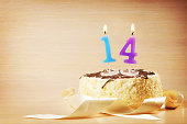 Birthday cake with burning candle as a number fourteen. Focus on the candle
