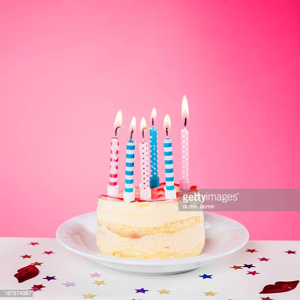 Birthday cake with candles standing on the table, pink background
