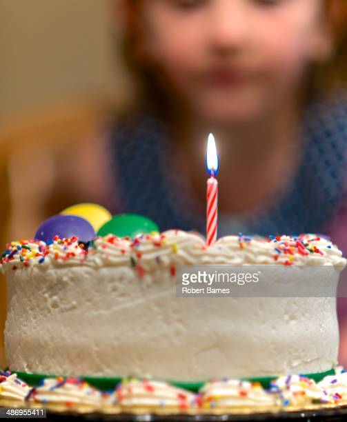 Birthday Cake with one lit candle and a child out of focus in the background