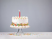 White Birthday cake with colorful Sprinkles and red candle over a gray background.