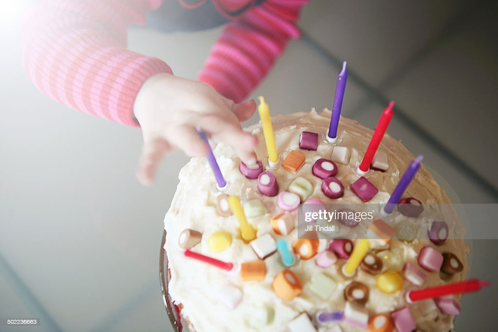 birthday cake with small child's hands exploring