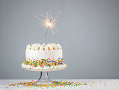 White Birthday cake with colorful Sprinkles and sparkler over a neutral background.