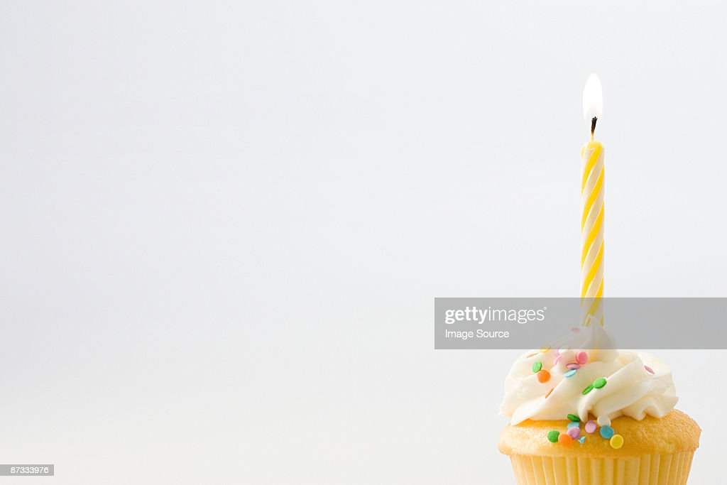Birthday candle on a cup cake : Stock Photo