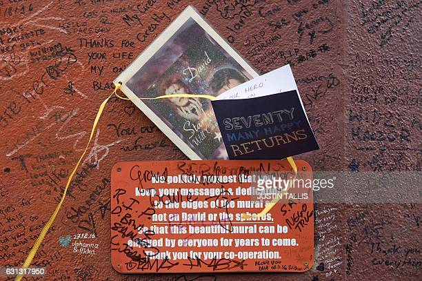 A birthday card is pictured in front of a mural of British musician David Bowie by Australian street artist James Cochran also known as Jimmy C in...