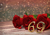 birthday concept with red roses on wooden desk. 3D render - sixty-nineth birthday. 69th