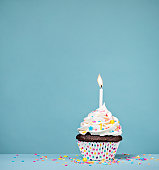 Birthday cupcake with sprinkles and a candle over a blue background.